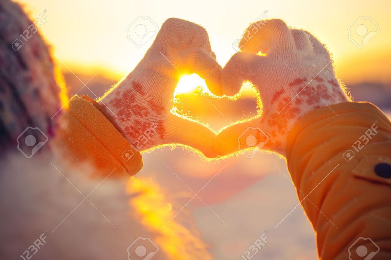 33571956-Frau-die-H-nde-in-den-Winterhandschuhen-Herzsymbol-f-rmigen-Lifestyle-und-Gef-hle-Konzept-mit-Sonnen-Lizenzfreie-Bilder