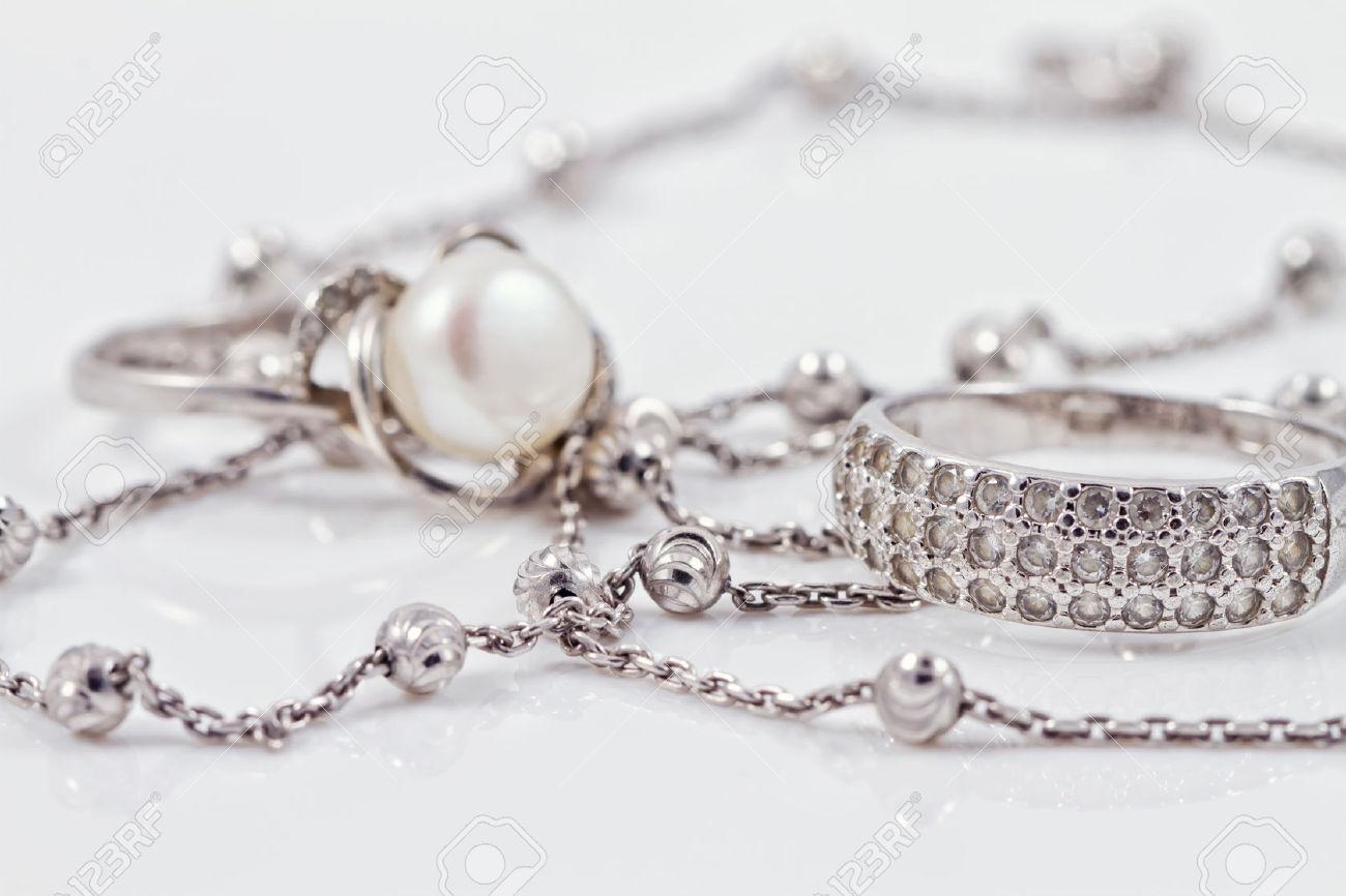 44106520-Silber-Ring-mit-Edelsteinen-und-Perlen-sind-zusammen-mit-einer-silbernen-Kette-auf-Acryl-Lizenzfreie-Bilder